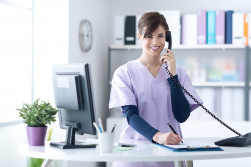 Dental assistant answering a call for appointment