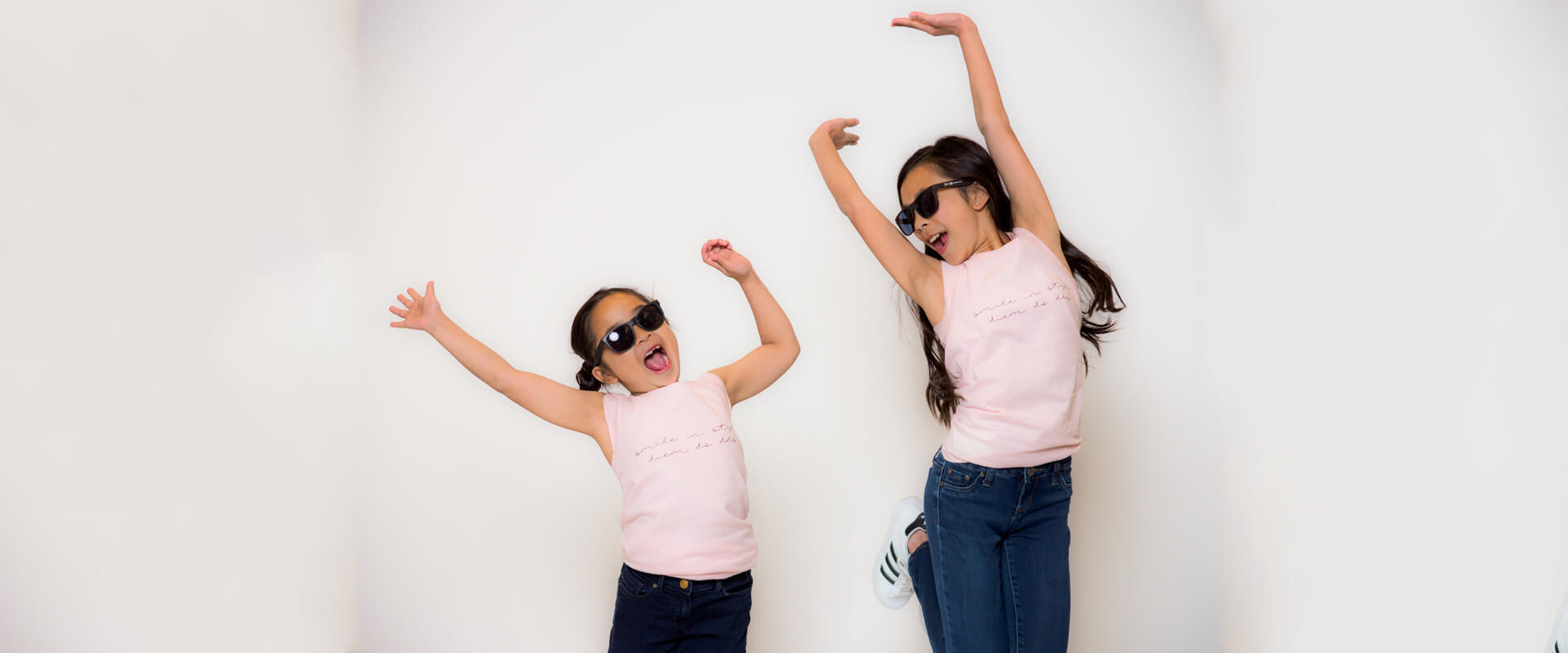 Two little girls smiling jumping in the air