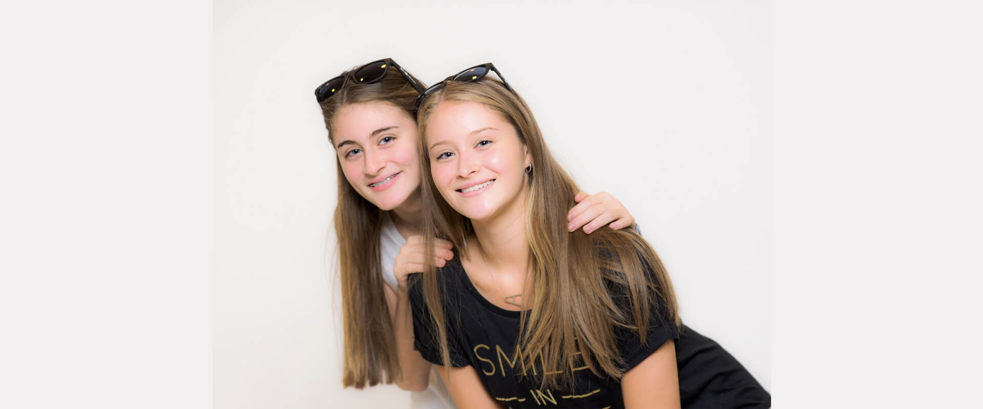 Two young ladies smiling aesthetically looking at the camera